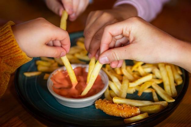 Chiuda sulle mani che tengono le patatine fritte