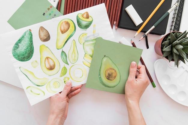 Mani del primo piano che tengono i disegni della frutta