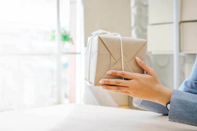 Close up hands holding gift box wrapped with kraft paper