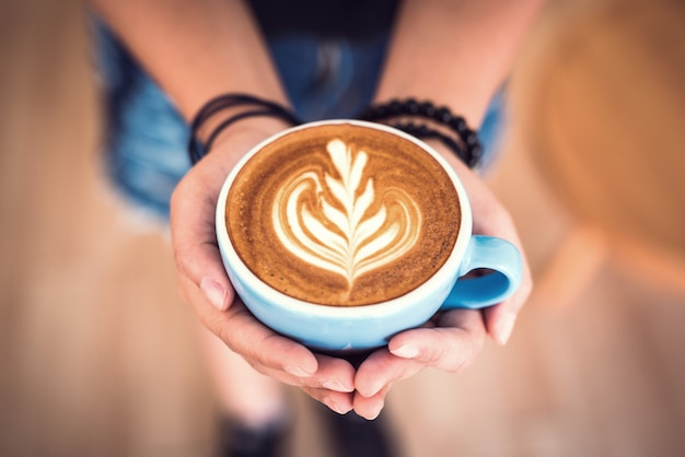 Close up hands holding hot cup of coffee latte