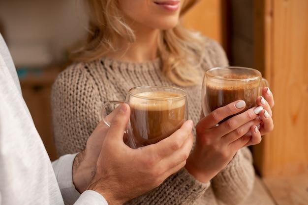 Mani del primo piano che tengono le bevande calde