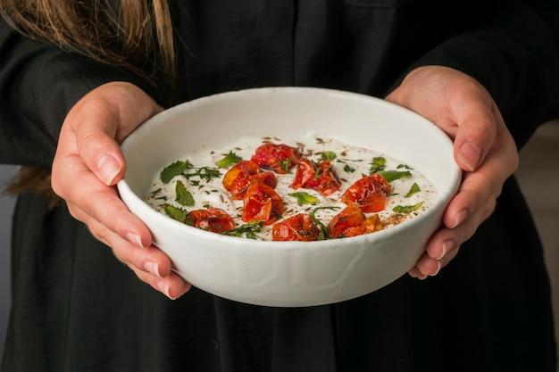 Крупным планом руки держат миску индийской еды