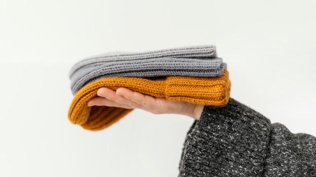 Mani del primo piano che tengono i cappelli lavorati a maglia