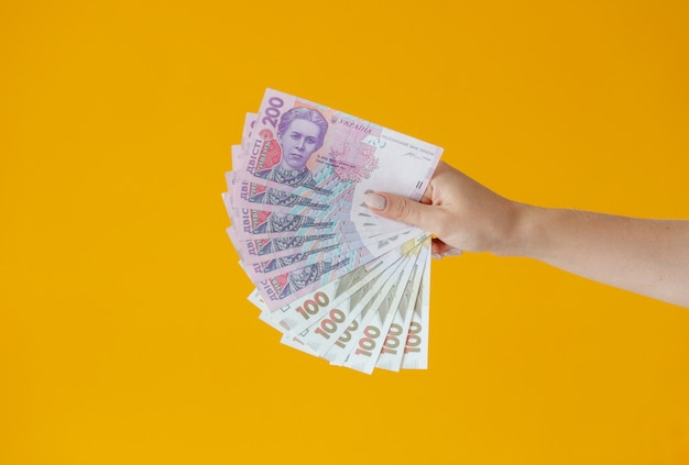 Close-up hands holding lots of money.  one hundred dollars banknotes and ukrainian hryvnia. background of business concept top view with copy space
