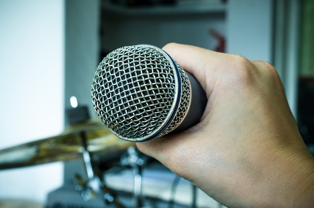 Close up of hands holding a microphone