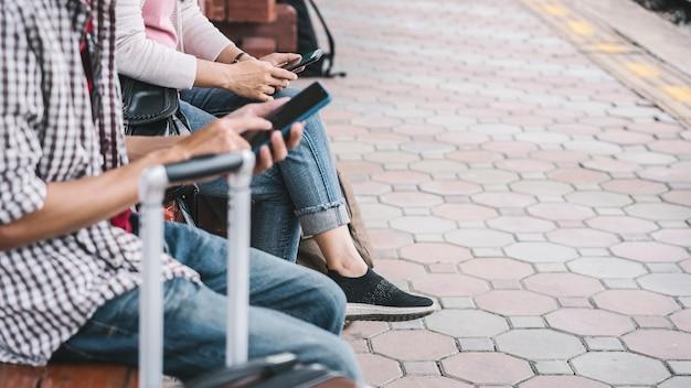 電車を待っているバッグとカップルの携帯を保持している手を閉じます。