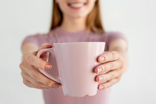 マグカップを保持しているクローズアップの手