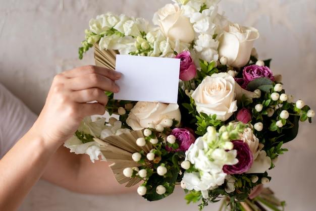 Mani ravvicinate che tengono nota e bouquet