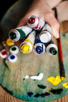Chiuda in su delle mani che tengono le pitture ad olio, parete della tavolozza