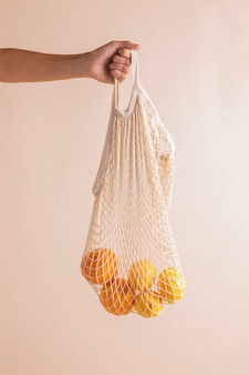 Mani del primo piano che tengono la borsa delle arance