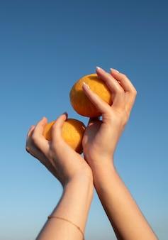 Chiudere le mani che tengono le arance