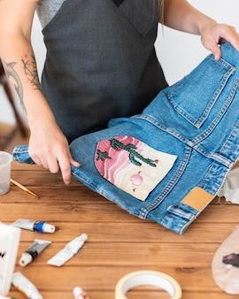 Mani del primo piano che tengono i pantaloncini dipinti