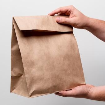 Mani del primo piano che tengono il sacchetto di carta