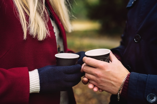 Close up of hands holding paper cups of coffee