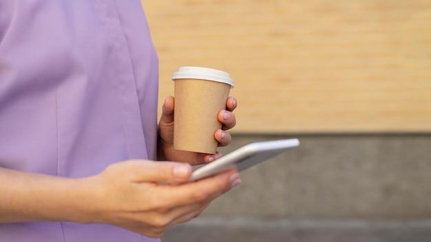 전화와 커피 컵을 들고 손을 닫습니다