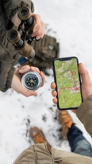 Close up hands holding phone and compass