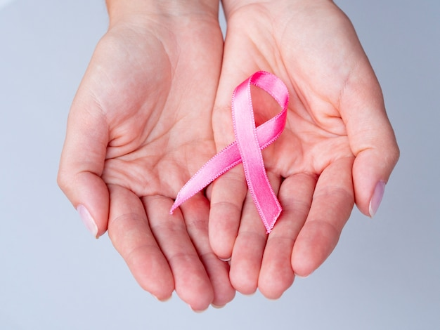 Close-up hands holding pink ribbon