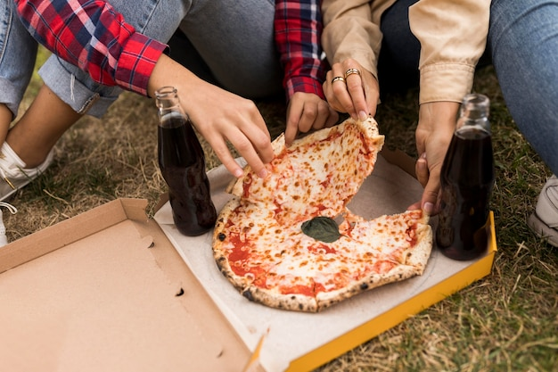 Mani del primo piano che tengono pizza