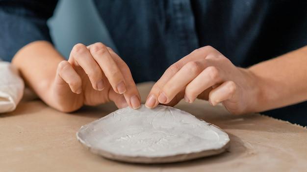 陶器アイテムを持っているクローズアップの手