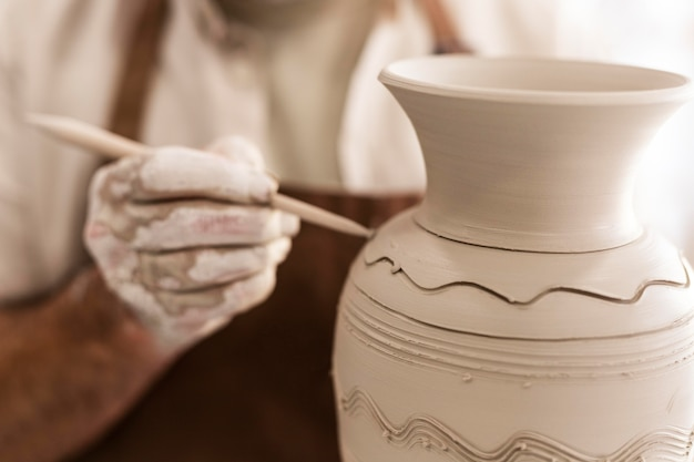 Закройте руки, держа инструмент керамики