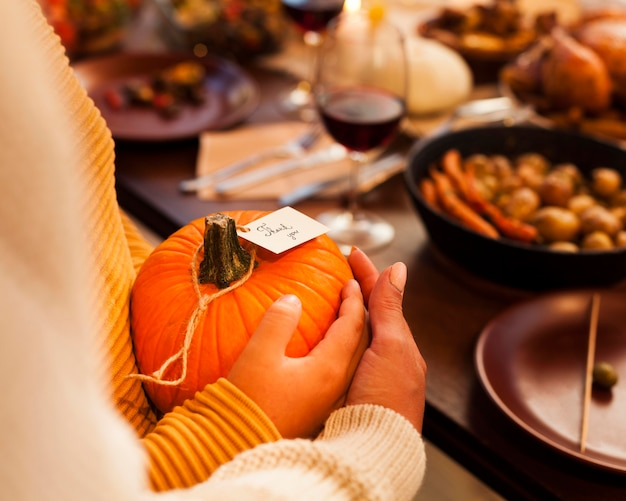 Close-up hands holding pumpkin at table