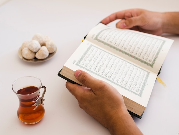 Close up of hands holding quran on table