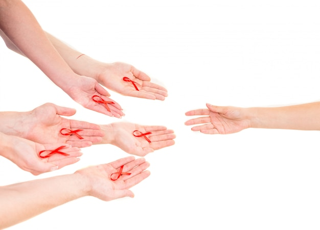 Close-up of hands holding red ribbons on white.