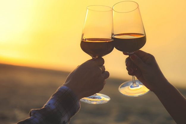 Close up on hands holding red wine glasses on the beach during sunset, celebration concept