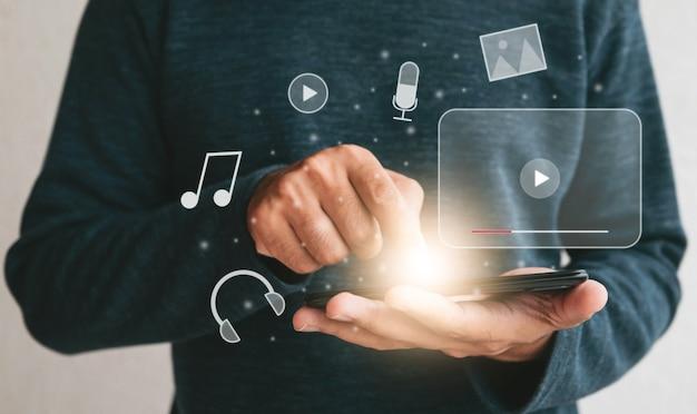 스마트폰을 들고 손을 닫습니다. 인터넷 라이브 콘서트 쇼 또는 tutorial.technology 비즈니스 투자 및 교육 개념에서 온라인으로 비디오를 시청하기 위해 휴대폰을 사용하는 남자