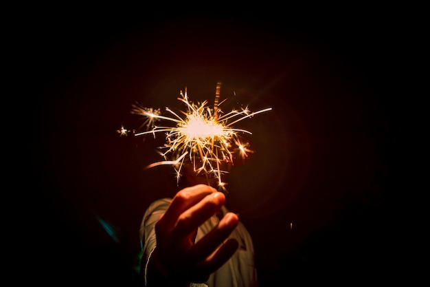 Close up of hands holding sparklers at night, firework celebrate at night