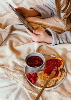 Крупным планом руки, держа планшет в постели
