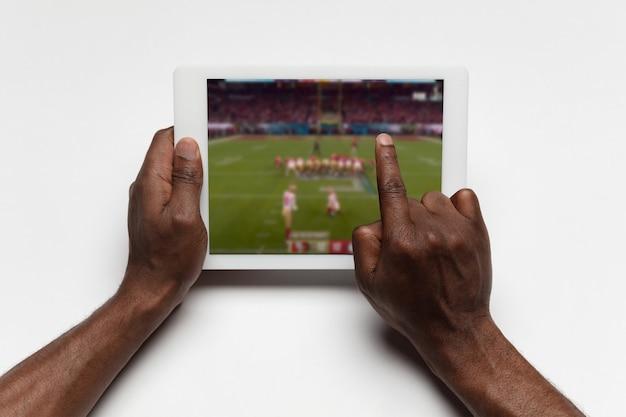 タブレット視聴スポーツ、チャンピオンシップのサッカーオンラインストリーミングを保持している手を閉じます。コロナウイルスの発生と国の封鎖中の新しい規則。スポーツ、競争、技術の概念。