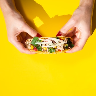 Close-up hands holding taco with yellow background