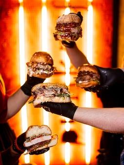 Крупным планом руки держат вкусный жареный бургер из говядины с салатом и майонезом. группа молодых людей, едят в фаст-фуде. друзья проводят время вместе в кафе, пивном баре или баре.