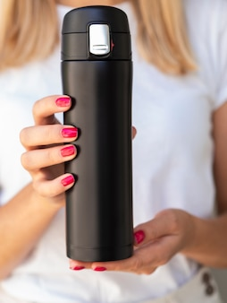 Close-up hands holding a thermos mock-up