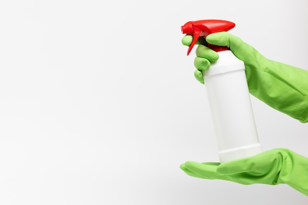 Close-up hands holding up white spray bottle