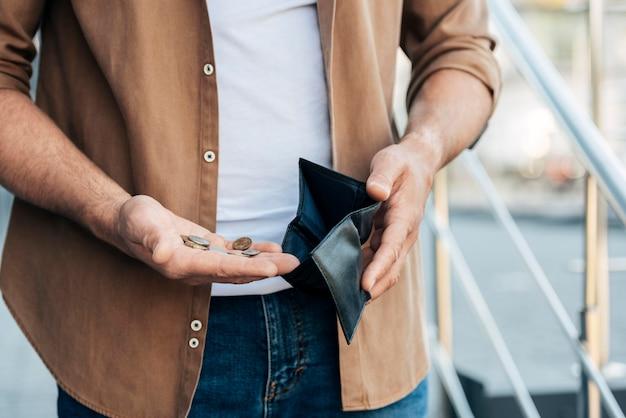 Mani del primo piano che tengono portafoglio e monete