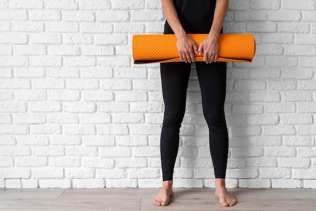 Mani del primo piano che tengono la stuoia di yoga