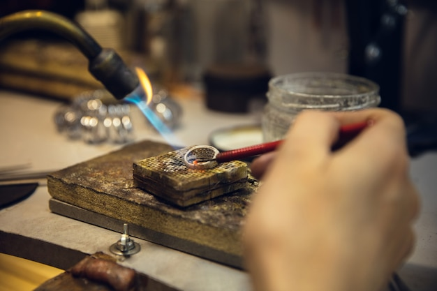 Close up hands of jeweller, goldsmiths making of golden ring with gemstone using professional tools