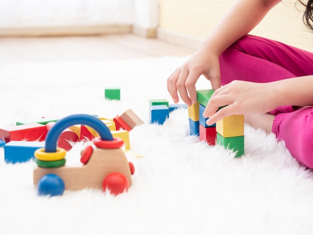 Close up hands of kid while playing wooden blocks on floor.