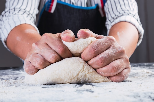 Close-up of hands kneading on a table.