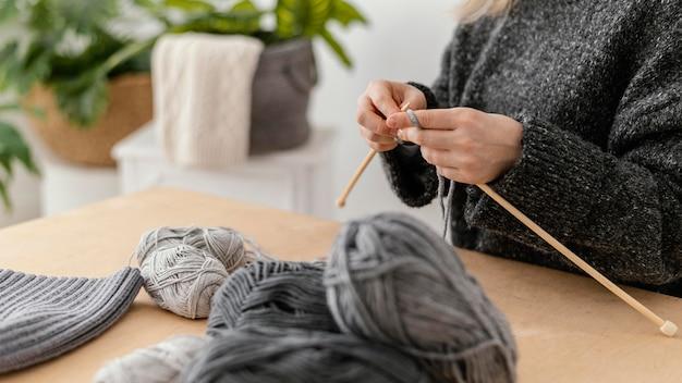 Mani del primo piano che lavorano a maglia con gli aghi