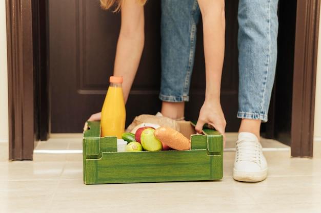 Крупным планом руки поднимают ящик с едой