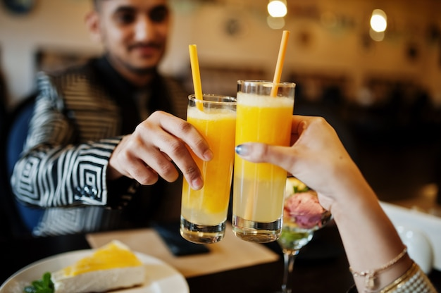 Close up hands of lovely couple in love, sitting on restaurant and cheers together by orange juice
