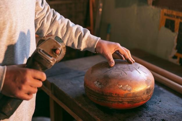 Mani del primo piano che fanno oggetto artigianale