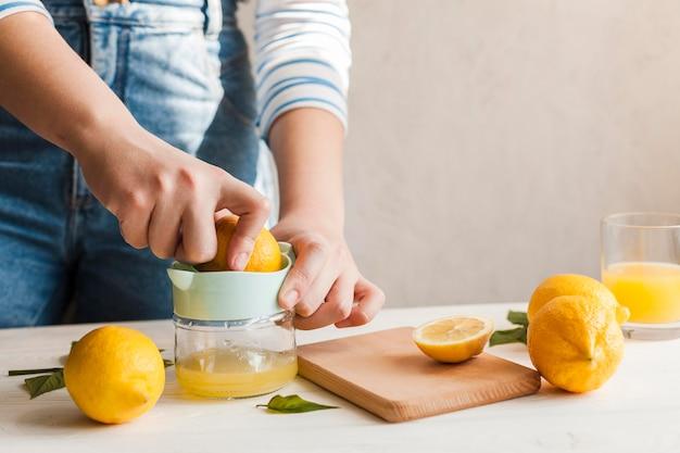 Mani del primo piano che producono il succo di limone