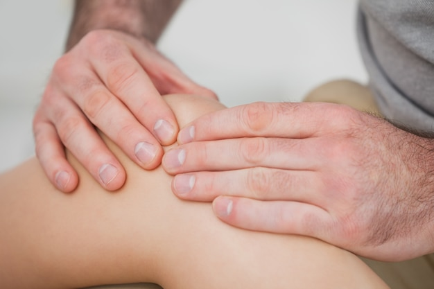 Close-up of hands making a massage on a knee