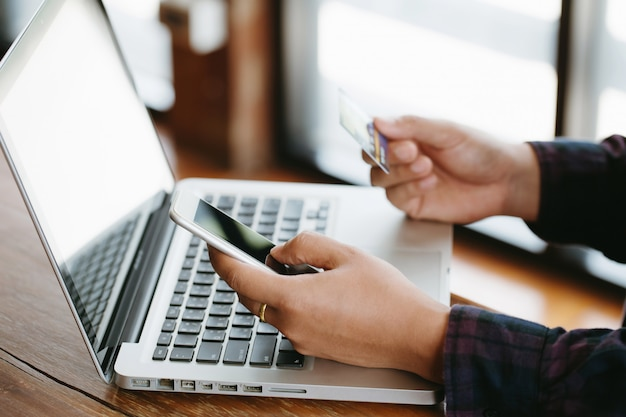 Close up hands making online payment. man's hands holding a credit card and using smart phone for online shopping