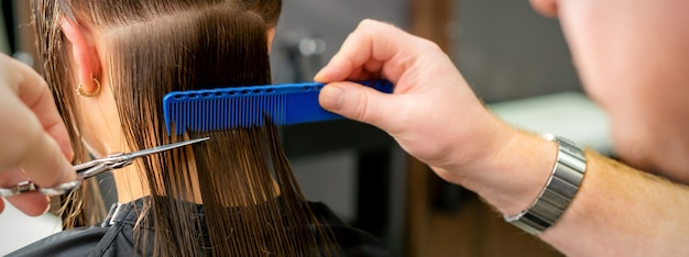 Close up of hands of male hairdresser cutting long hair of young woman holding scissors and comb at the salon