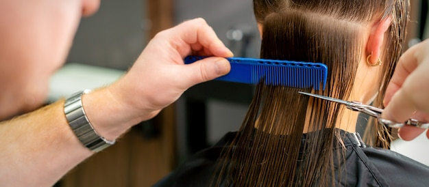 Close up of hands of male hairdresser cutting long hair of young woman holding scissors